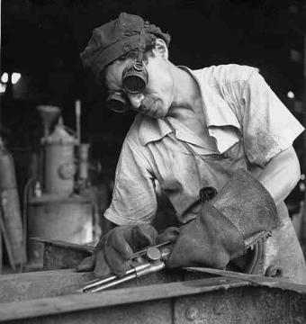 Trabajador soldando el marco de un tren de mercancías de la American Railroad Co. Porto Rico en San Juan, Puerto Rico